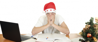 Sleepy student wearing santa hat while studying