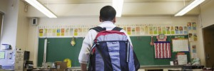 boy wearing backpack in school