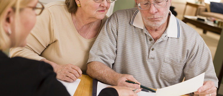 elderly couple looking at papers