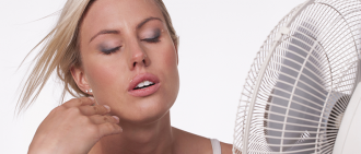woman cooling off in front of fan