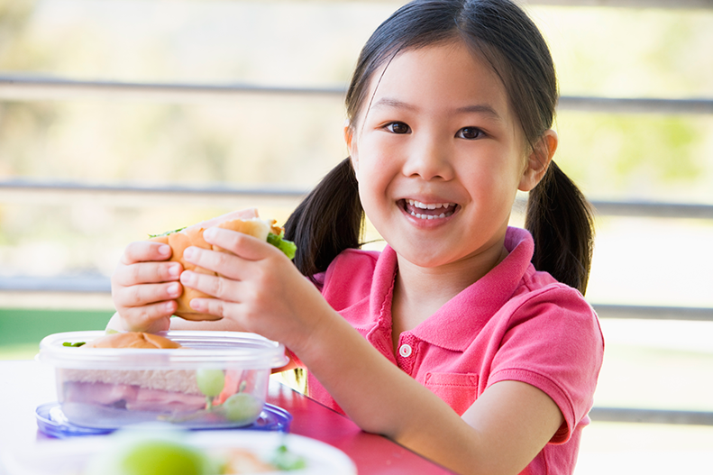 young girl eating sandwhich