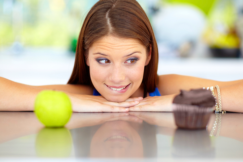 woman choosing between apple and cupcake