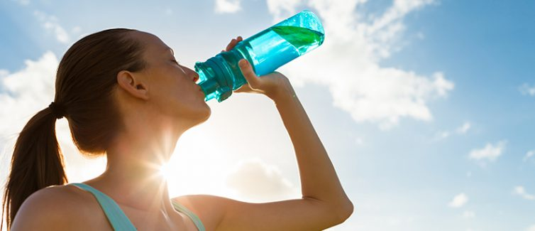 Woman drinking water to show the importance of hydration for athletes