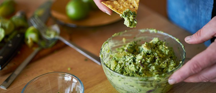dipping a tortilla chip in guac