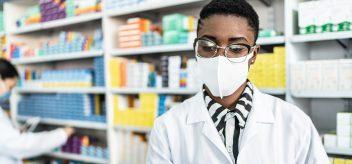 在药房工作的戴口罩的女药剂师